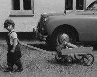 Photo of young Linda O'Neil with early vehicles